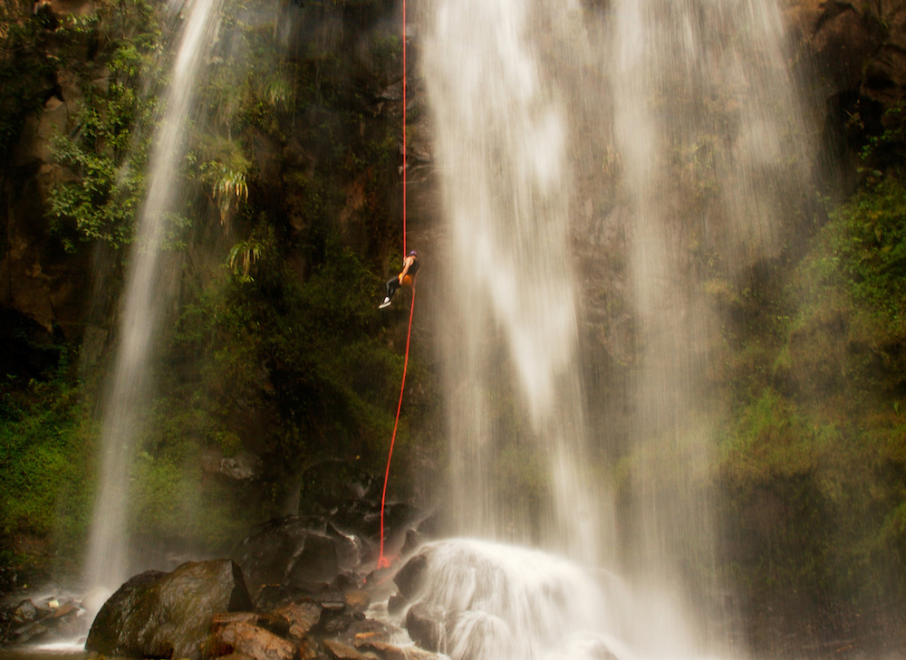 An adventurer repels one of the many dramatic waterfalls that line the rugged flanks of the Andes Mountains that lead to the Ecuadorian flatlands known as El Oriente.