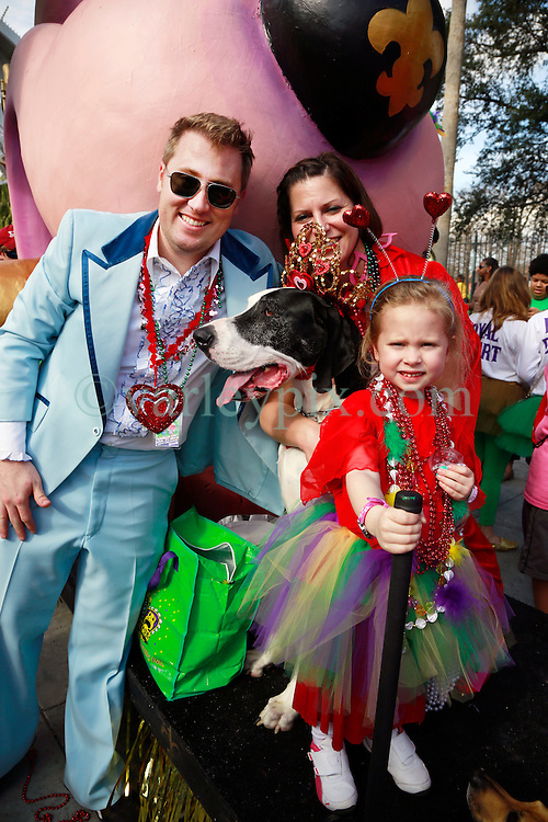 27 Jan 2013. New Orleans, Louisiana USA. .The Mystic Krewe of Barkus. Queen of Barkus, Hattie the dog with owners Chris and Amanda Warner with daughter Charlotte (4 yrs).Following the theme 'Here Comes Honey Bow Wow,' the parade parodies a popular media title as dogs and their owners parade through the French Quarter in one of the most irreverent parades of the season..Photo; Charlie Varley