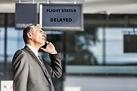 Mature businessman making report on his delayed flight while standing at his boarding gate in airport