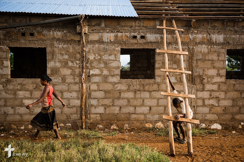 A man descends a ladder after working on a piece of tin roof at the Amboasary -1 Fiangonana Loterana Malagasy (FLM, Malagasy Lutheran Church) church on Monday, Oct. 20, 2014, near Amboasary, Madagascar. LCMS Communications/Erik M. Lunsford