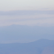 Rows of mountains in the distance as seen from the rim of the Ngorongoro Crater in the Ngorongoro Conservation Area, part of Tanzania's northern circuit of national parks and nature preserves.