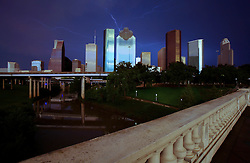 Lightning in night sky over Houston, Texas skyline with Sabine Bridge and Buffalo Bayou in foreground.