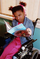 Young woman with Cerebral Palsy reading cookbook in residential care centre,