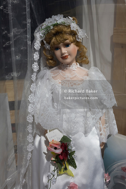 Holding a tiny bouquet of flowers, a small bride doll is on display in the window of a small antique shop in the Somerset town of Burnham-on-sea.
