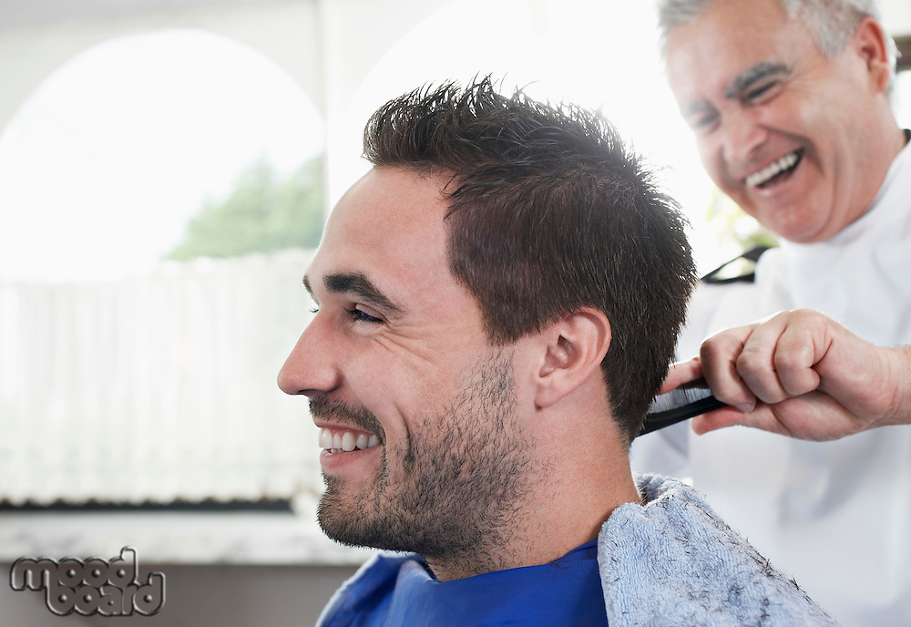 Barber cutting mans hair in barber shop close-up