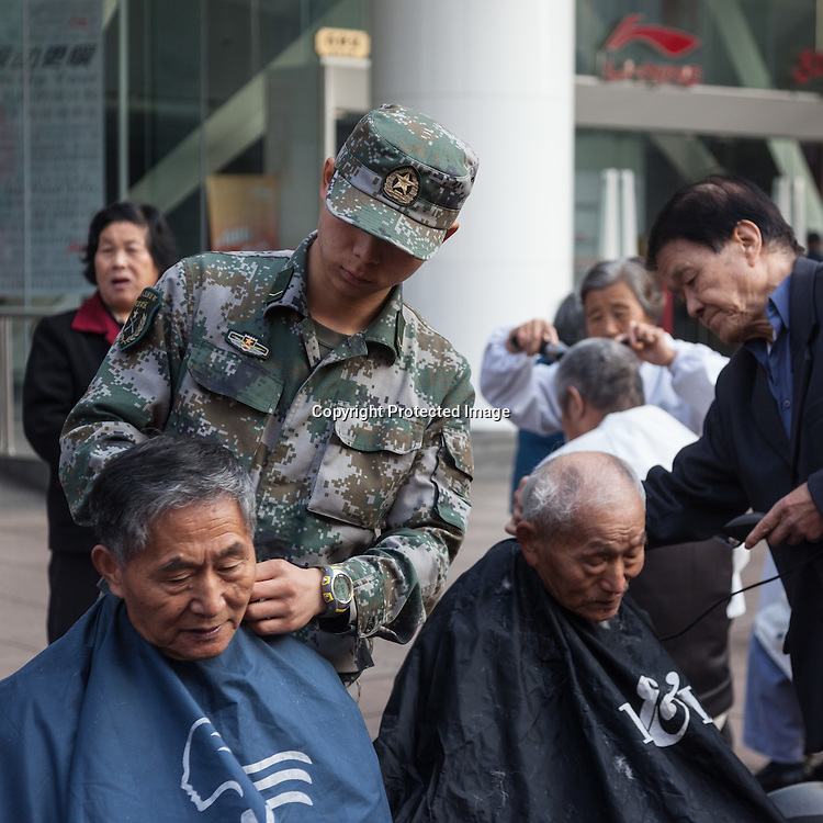 China, Shanghai. red Cross day on Nanjing street; Chinese army soldier hairdresser