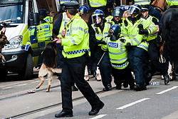 The English Defence League (EDL) return to Sheffield to lay flowers at Sheffield War Memorial . resulting in a police operationlasting over 5 hours involving Officers from Wales, South Yorkshire, Greater Manchester, West Yorkshire, Lancashire and Mersyside Police forces.  As police move the Anti EDL demonstrators back down West Street towards Barkers Pool an injured Officer from Greater Manchester Police is brought back behind Police lines<br /> <br /> 8 June 2013<br /> Image © Paul David Drabble<br /> www.pauldaviddrabble.co.uk