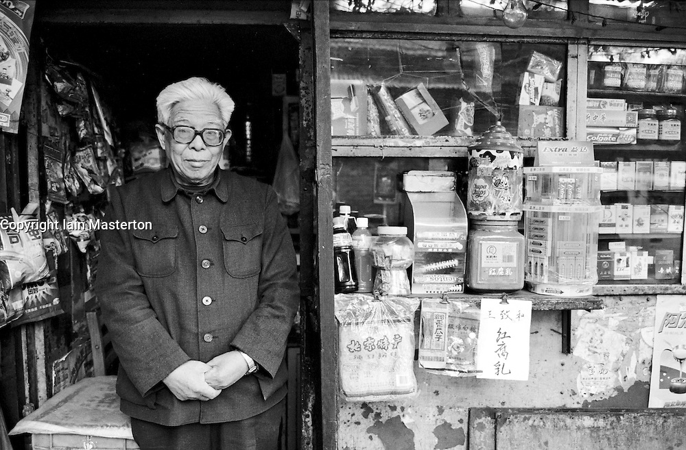 Shopkeeper stands beside his shop in a traditional old Beijing hutong