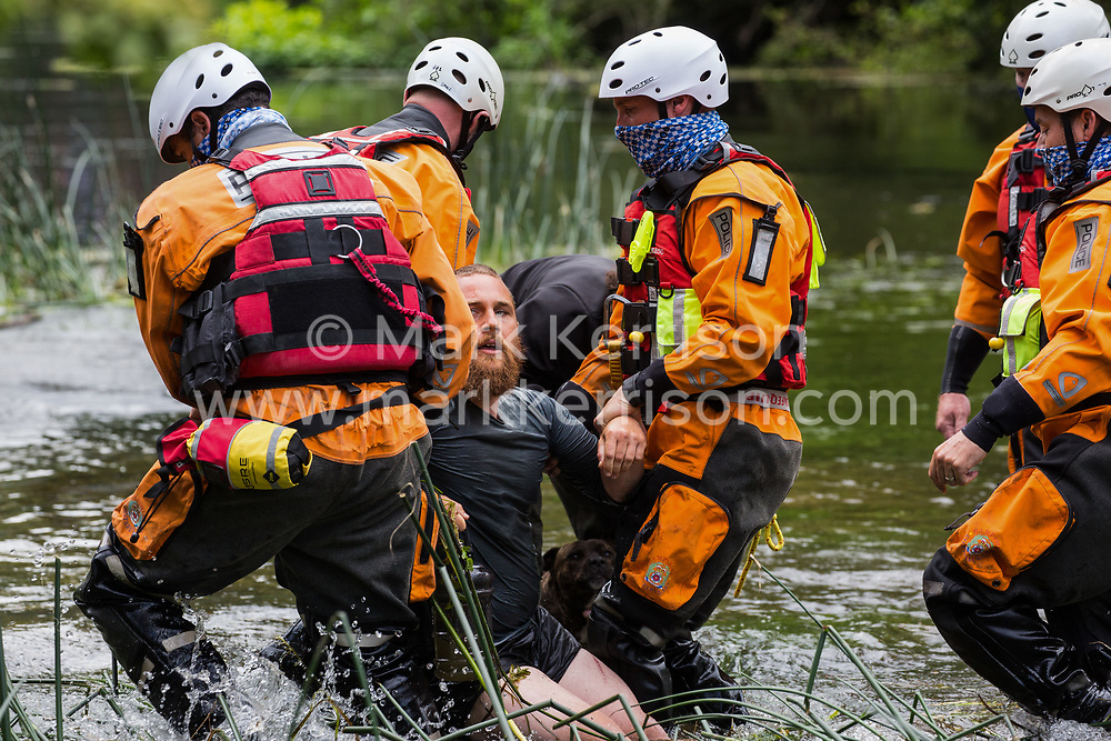 Denham, UK. 24 July, 2020. Police officers from Hampshire Police Marine Support Unit remove a male activist from HS2 Rebellion from the river Colne for arrest after he had tried to hinder the destruction of an ancient alder tree in connection with works for the HS2 high-speed rail link in Denham Country Park. A large policing operation involving the Metropolitan Police, Thames Valley Police, City of London Police and Hampshire Police as well as the National Eviction Team was put in place to enable HS2 to remove the tree.
