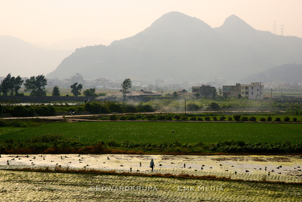Rural blends into city as a farms along the highway merge with residential dwellings. Eastern China.