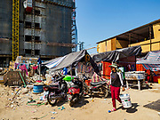 """15 FEBRUARY 2019 - SIHANOUKVILLE, CAMBODIA: A Cambodian construction laborer walks through worker housing next to the site of the Chinese casino construction site she works at. There are about 80 Chinese casinos and resort hotels open in Sihanoukville and dozens more under construction. The casinos are changing the city, once a sleepy port on Southeast Asia's """"backpacker trail"""" into a booming city. The change is coming with a cost though. Many Cambodian residents of Sihanoukville  have lost their homes to make way for the casinos and the jobs are going to Chinese workers, brought in to build casinos and work in the casinos.    PHOTO BY JACK KURTZ"""