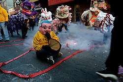 Fireworks go off as lions dance around the 'clown', or 'lion tamer', here performed by wel-known Chinatown resident Albert Lee.