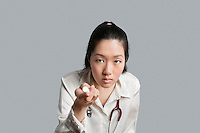 Young Asian female doctor holding a flashlight over gray background