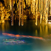 Swimmers enjoy the crystal clear waters of  Cenote X'kakah near Valladolid (also near Dzitnup). Part of the Yucatan's massive network of underground waterways that pass through the porous limestone, Cenote X'kakah is a popular underground swimming hole. It has a small opening in the ceiling that lets in light, fresh air, and even a little rain, and impressive stalactites hanging from the ceiling. The water temperature is a constant 76 degrees fahrenheit year round. The swimmers in this shot are blured by a long exposure and are wearing bright orange lifevests.