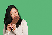 Portrait of a young woman eating a large chocolate bar over green background