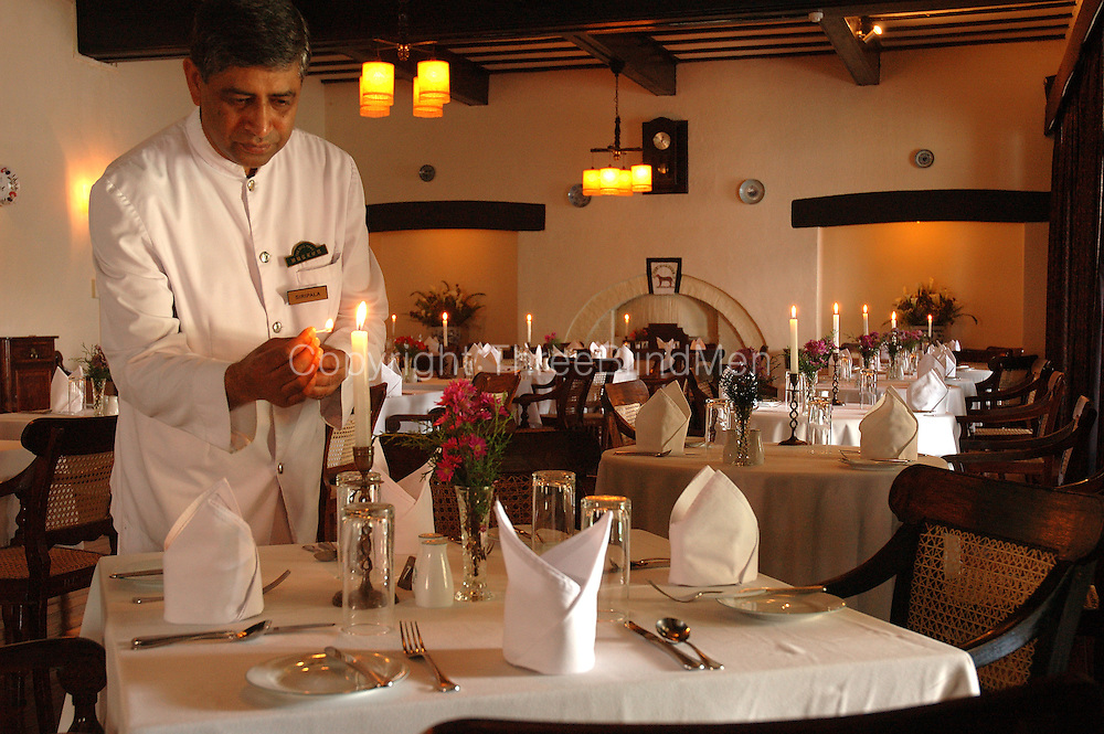 Mr. Siripala, Head Butler, lights the candles for the evening meal. The Hill Club in Nuwara Eliya.