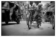 Wallah pulling rickshaw up Varanasi street.