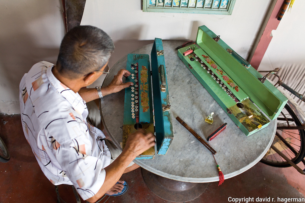 Uncle Soon (Fong Ching Soo, who was born on Armenian St) plays a traditional stringed instrument in his bicycle shop on Armenian St.