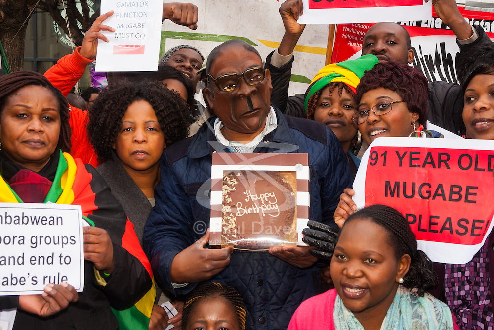 """Lodon, February 21st 2015. Dozens of exiled Zimbabweans gather outside their embassy in London proclaiming Mugabe's last birthday in office. Singing and dancing as they have done every Saturday since 2002, the group spoke with passersby and added yet more names to their petition. PICTURED: """"Mugabe"""" displays his birthday cake as back in Zimbabwe hundreds of guests prepare to dine on two elephants that have allegedly been butchered for his birthday celebrations at Victoria Falls."""