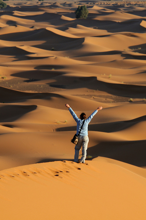 A man is standing at the top of a dune in a sand desert and is feeling the freedom and the love of life. Merzouga. Morocco. Africa.