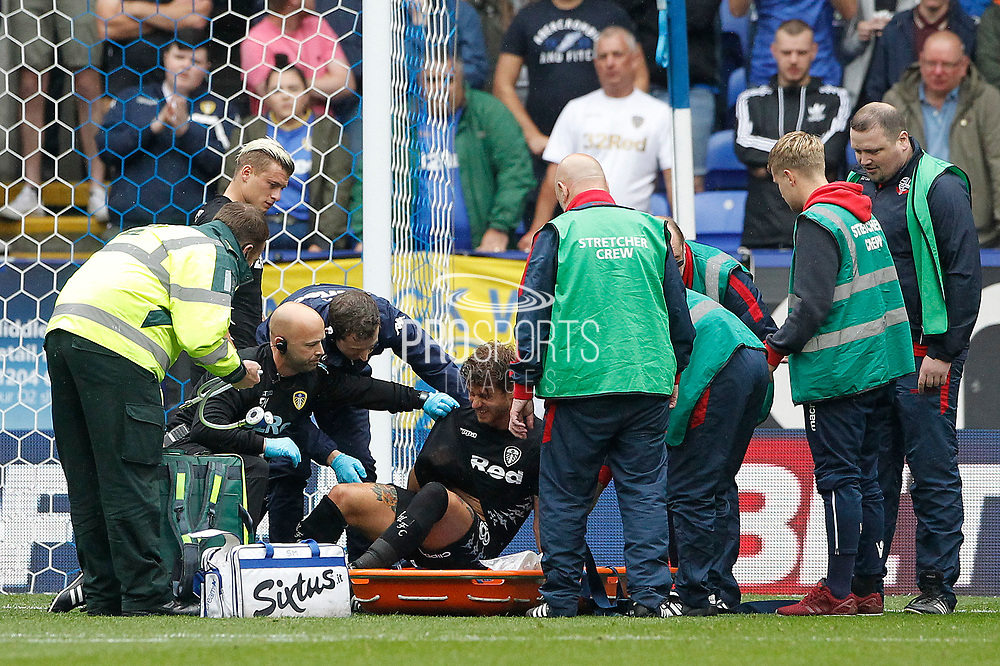 Leeds United Gaetano Berardi (28) game is over as he is helped onto the stretcher during the EFL Sky Bet Championship match between Bolton Wanderers and Leeds United at the Macron Stadium, Bolton, England on 6 August 2017. Photo by Craig Galloway.