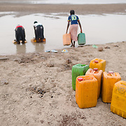 Jerry cans of water waiting to be loaded onto a donkey cart as Rihanata Ouedraogo (15, centre) and her sisters, Alimata (18, left) and Nafisatou (17) collect water from a dam in Koala, Burkina Faso on 1 March 2014. The girls typically make three round trips every day, filling 17 jerry cans each time, with each trip taking over an hour.