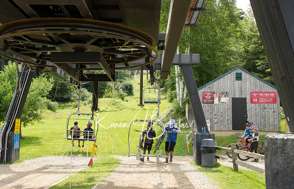 Riders easily hoist their bikes onto the chairlift as they take the ride to the summit at Highland Mountain Bike Park in Northfield.  (Karen Bobotas/for the Laconia Daily Sun)