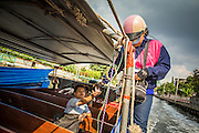 14 NOVEMBER 2012 - BANGKOK, THAILAND:  A ticket taker and fare collector holds onto a the safety rope while she collects ticket money from a passenger on a boat on Khlong Saen Saeb in Bangkok. Bangkok used to be criss crossed by canals (called Khlongs in Thai) but most have been filled in and paved over. Khlong Saen Saeb is one of the few remaining khlongs in Bangkok with regular passenger boat service. Boats and ships play an important in daily life in Bangkok. Thousands of people commute to work daily on the Chao Phraya Express Boats and fast boats that ply Khlong Saen Saeb. Boats are used to haul commodities through the city to deep water ports for export.      PHOTO BY JACK KURTZ