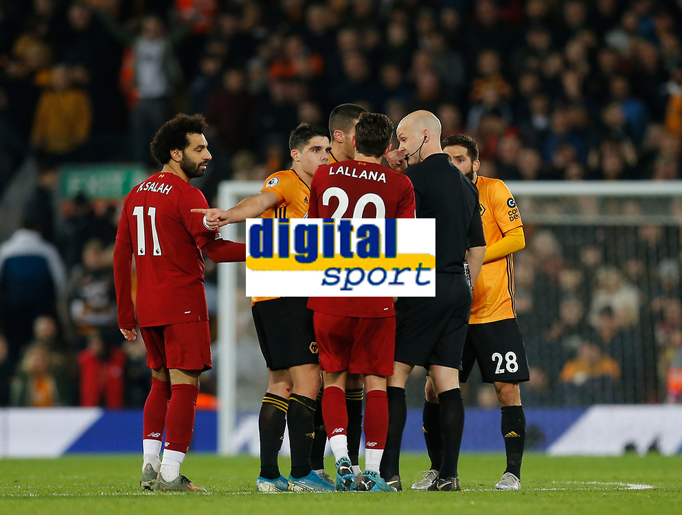 Football - 2019 / 2020 Premier League - Liverpool vs. Wolverhampton Wanderers<br /> <br /> The players surround referee Anthony Taylor after VAR upholds the Liverpool winner, at Anfield.<br /> <br /> COLORSPORT/ALAN MARTIN