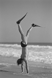 man on the beach doing a handstand wearing a speedo and flippers