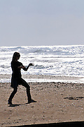 Silhouette of a woman doing Tai Chi on the beach
