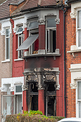 © Licensed to London News Pictures. 16/04/2020. London, UK. The front of a house on Alric Avenue with a fire damaged facade. The Metropolitan Police Service were called at 02:15BST to a residential address in Alric Avenue NW10 following reports of a fire. Police officers attended with the London Fire Brigade (LFB) and London Ambulance Service (LAS). A 36-year-old woman was taken to hospital with serious injuries. She was pronounced dead at 06:07BST. Another woman, aged in her 60s, was also taken to hospital and treated for non life-threatening injuries. A man in his 40s was arrested on suspicion of arson and taken into police custody. Photo credit: Peter Manning/LNP