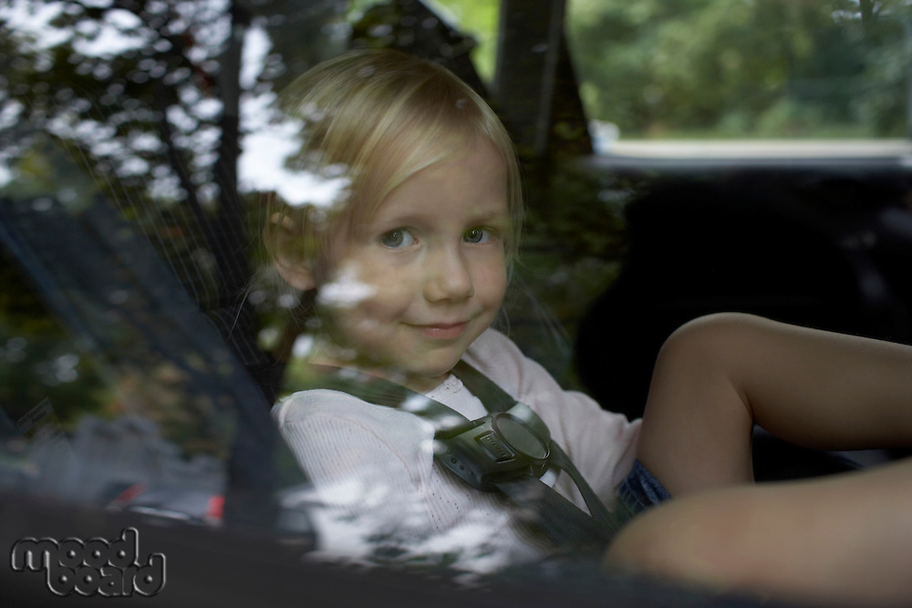 Pre-teen girl looking through car window