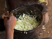 Elile Banga, 15, cooking fresh cabbage for lunch outside her home in Boreda, Ethiopia. Elile is in 7th grade at school and she would like to become a doctor.