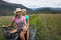 Two women riding four-wheeler through field
