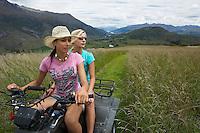 Two women riding four-wheeler through field