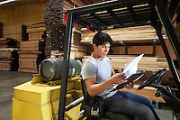 Forklift Driver in Warehouse Looking at Paperwork