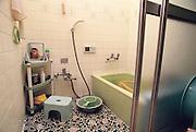 Kazuo Ukita relaxes in an ofuro (a Japanese bath that is meant for relaxation rather than washing). The water is generally kept in the tub and warmed before each use. Family members wash squatting on a stool with a bucket of hot water and a shower hose before entering the bath. When not in use the bath is covered with an insulated cover. Japan. Material World Project. The Ukita family lives in a 1421 square foot wooden frame house in a suburb northwest of Tokyo called Kodaira City.