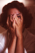Woman with hands covering face, one eye visible.  Elaine.