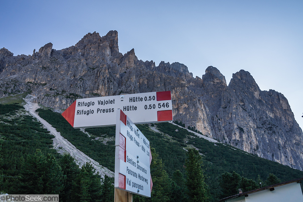 A trekking sign directs hikers to Rifugio Vajolet Hutte beneath Dirupi di Larsec (2890m) in the Rosengarten/Catinaccio group in the Dolomites, Italy, Europe. From Pera di Fassa village (in Pozza di Fassa comune in Val di Fassa), in Trentino-Alto Adige/Südtirol region, Italy, take a bus or lift to visit Rifugio Gardeccia Hutte and hike in the Rosengarten mountain massif (Catinaccio Group) of the Dolomites. 200 million years ago, Triassic coral reefs fossilized into Dolomite. Collision of tectonic plates lifted the Dolomites within the Southern Limestone Alps. UNESCO honored the Dolomites as a natural World Heritage Site in 2009.