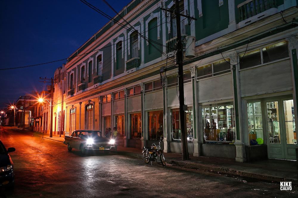 Old American car parked in a dark street at Calle 31, Pueblo Nuevo neighborhood in Cienfuegos