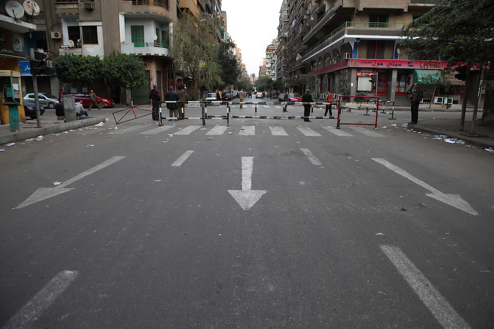 Neighborhood watch roadblocks in an area of downtown Cairo destroyed after protesters clashed with police on the previous day. .