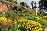 A late summer border of hot colours:  helianthus, penstomen and helenium next to a wall at Cliveden, Taplow, Berkshire