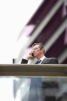 Businessman using mobile phone in front of building low angle view