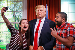 © Licensed to London News Pictures. 18/01/2017. London, UK. A couple pose with a wax figure of the US President-elect Donald Trump as it is being prepared for unveiling at Madame Tussauds in London ahead of the US Presidential Inauguration on Wednesday, 18 January 2017. Photo credit: Tolga Akmen/LNP