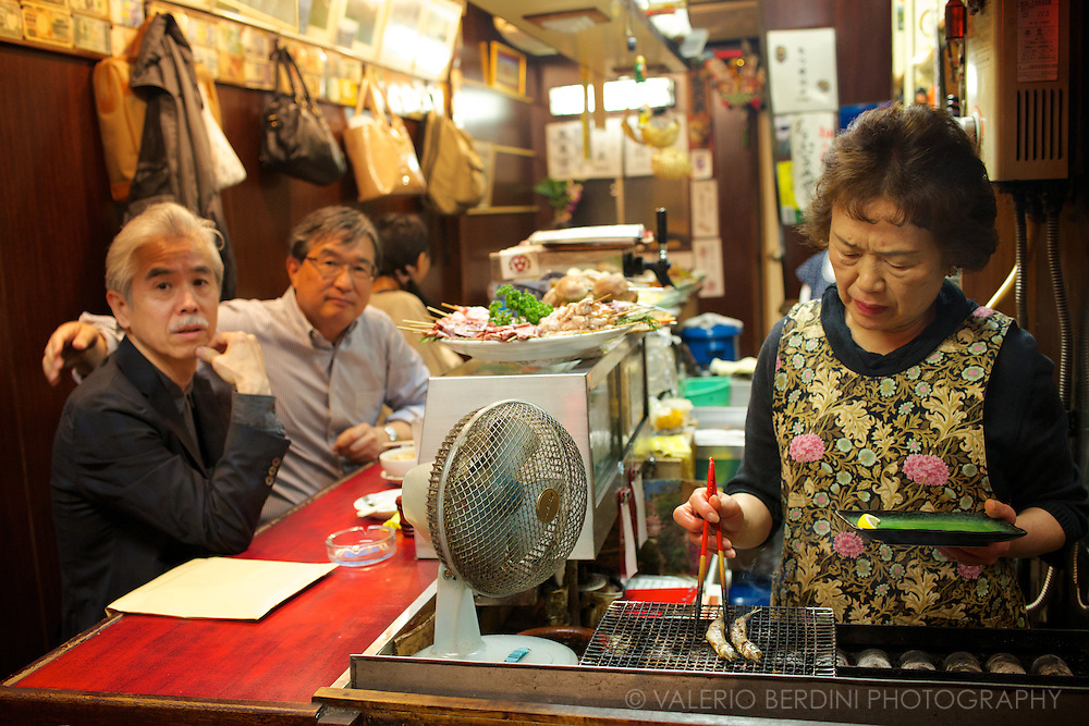 A woman grills some fishes for two friends having a snack in one of the tiny yakitori restaurants of Memory Lane. Close to Shinjuku station, Tokyo. Japan.