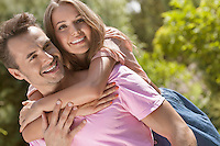 Happy young man giving piggyback ride to woman in park