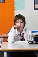 Boy (10-12) wearing shirt and tie in classroom portrait