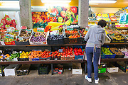 SANTIAGO DE COMPOSTELA, SPAIN - 13th October 2017 - Local grocer stacks shelves with fresh produce at a fruit and veg market, Santiago de Compostela, Galicia, Spain.