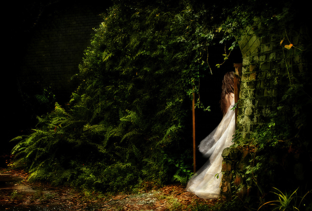 A young woman wearing a long white dress only partially visible passing through an arch doorway outdoors with foliage
